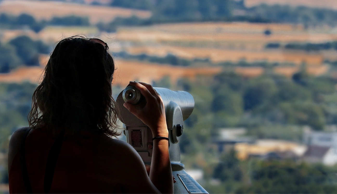 Young woman at a viewpoint looking through binoculars trying to find the best real estate agent in Colorado