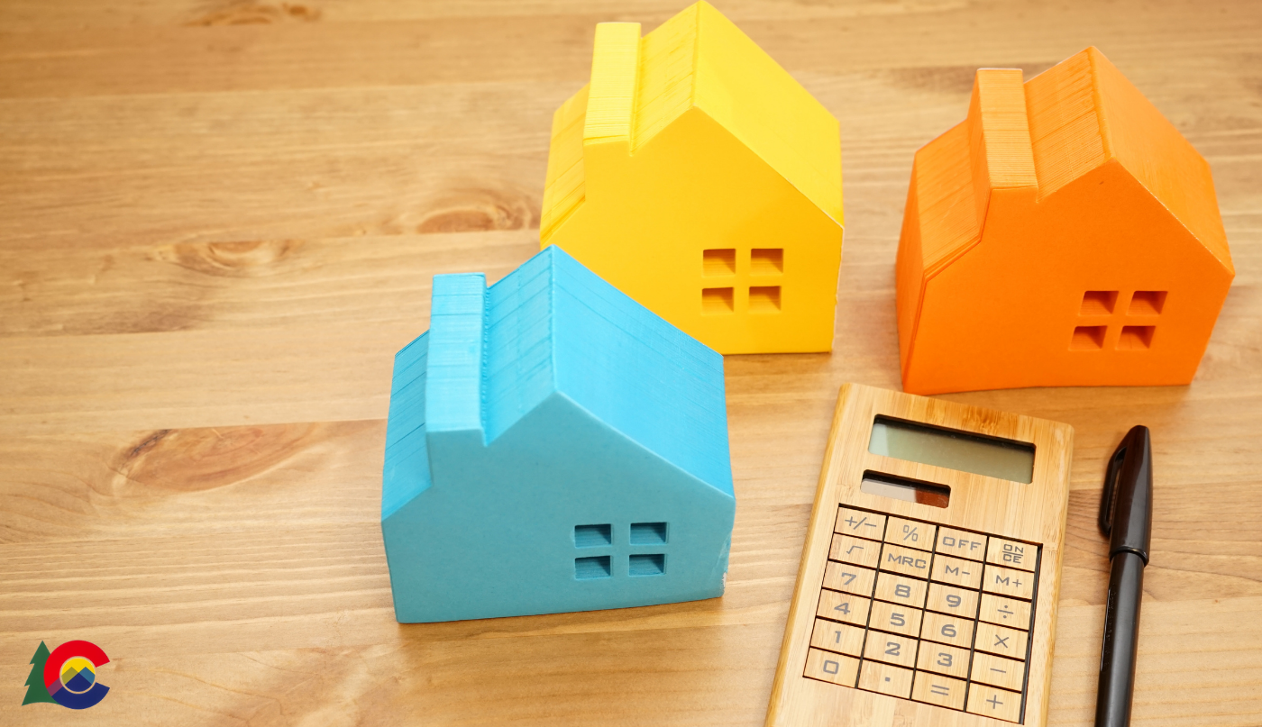 Three toy model homes placed on a table next to a calculator and pen to calculate realtor commission fees in Colorado